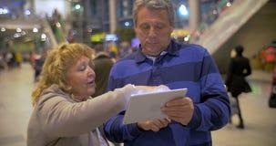 Senior couple having vivid talk using pad at the stock video footage