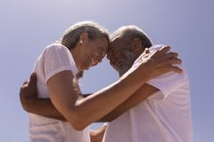 Senior couple head to head and embracing each other on beach royalty free stock photos
