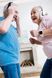 Senior couple in headphones dancing together at home stock photos