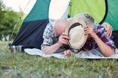 Senior couple hiding behind a hat. Silly senior couple in tent is hiding behind a hat at the campsite royalty free stock photo