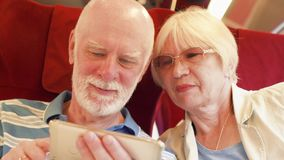 Senior couple in high-speed international train using smartphone. Active modern life after retirement. Senior couple traveling in Europe. Retired family relaxing stock footage