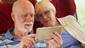 Senior couple in high-speed international train using smartphone. Active modern life after retirement. Senior couple traveling in Europe. Retired family relaxing stock video footage