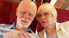 Senior couple in high-speed international train using smartphone. Active modern life after retirement. Senior couple traveling in Europe. Retired family relaxing stock video
