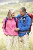Senior Couple On Hike Through Beautiful Countryside Stock Photography