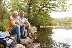 Senior Couple On Hike Sitting By River In UK Lake District stock image