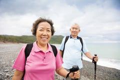 Senior couple hiking on the coast beach Royalty Free Stock Photo