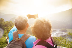 Senior couple hiking on mountains and taking selfies Stock Photography