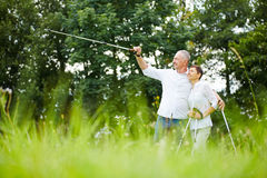 Senior couple hiking and pointing to the distance Stock Image