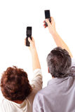 Senior couple hold mobile phones in hand Royalty Free Stock Images