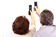 Senior couple hold mobile phones in hand Stock Photography