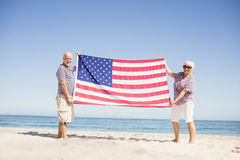 Senior couple holding american flag together. On beach Stock Photo