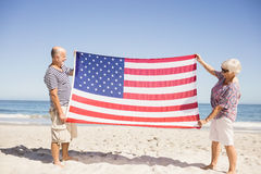 Senior couple holding american flag together. On beach Royalty Free Stock Photo