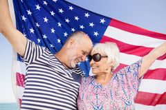 Senior couple holding american flag together. On beach Royalty Free Stock Photography