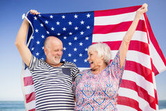 Senior couple holding american flag together. On beach Royalty Free Stock Images