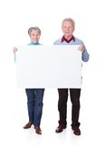 Senior couple holding blank placard Stock Images
