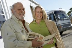 Senior Couple Holding A Brochure. Portrait of happy senior couple holding a brochure with bus in background Stock Image