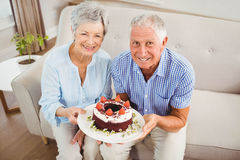 Senior couple holding a cake Stock Image