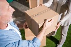 Senior couple holding cardboard box while moving into new house Royalty Free Stock Image
