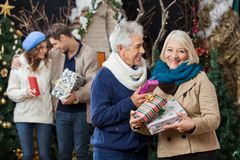 Senior Couple Holding Christmas Presents With Royalty Free Stock Image