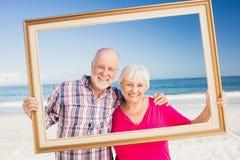 Senior couple holding frame Stock Images