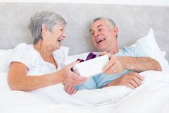 Senior couple holding gift box in bed Stock Image