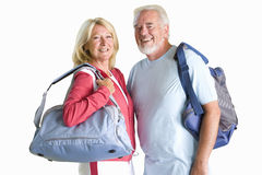Senior couple holding gym bags in sports clothing, cut out Stock Photos