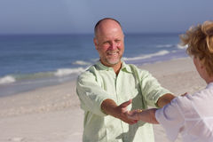 Senior couple holding hands on beach, smiling at each other Stock Photo