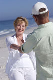 Senior couple holding hands on beach, smiling at each other Royalty Free Stock Photos