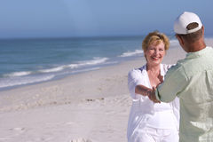 Senior couple holding hands on beach, smiling at each other Royalty Free Stock Image