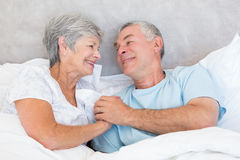Senior couple holding hands in bed Royalty Free Stock Photos