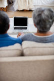 Senior couple holding hands while looking at the laptop Stock Image