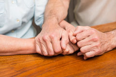 Senior couple holding hands on table Stock Photo