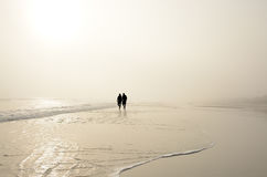 Senior couple holding hands walking on beach enjoying sunrise. Senior couple holding hands walking on beautiful foggy beach at sunrise, Sun and    clouds Stock Photo