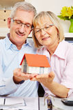 Senior couple holding house on their hands. Happy senior couple holding a small house on their hands Royalty Free Stock Photography