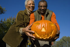 Senior couple holding jack-o-lantern Royalty Free Stock Photos