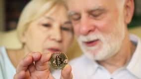 Senior couple holding and looking at cryptocurrency bitcoin. Shiny virtual money of online trade