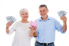 Senior couple holding money and piggy bank Royalty Free Stock Photography