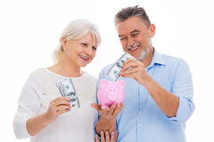 Senior couple holding money and piggy bank. Portrait of senior couple standing over white background Royalty Free Stock Photo
