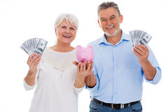 Senior couple holding money and piggy bank. Portrait of senior couple standing over white background Royalty Free Stock Photography