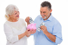 Senior couple holding money and piggy bank. Portrait of senior couple standing over white background Royalty Free Stock Image