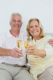 Senior couple holding out champagne flutes at home Royalty Free Stock Photography