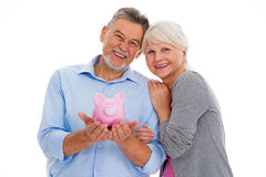 Senior couple holding piggy bank. Portrait of senior couple standing over white background Stock Photos