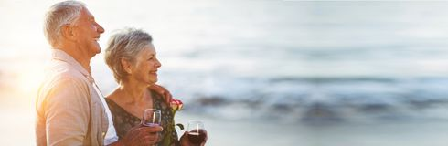 Senior couple holding rose and red wine glasses. At the beach Stock Image