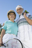 Senior Couple Holding Tennis Racquet And Balls. Portrait of happy senior couple holding tennis racquet and balls against clear sky Stock Photography