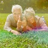 Senior couple holding thumbs up royalty free stock photos