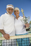 Senior Couple Holding Trophy At Tennis Net Stock Images