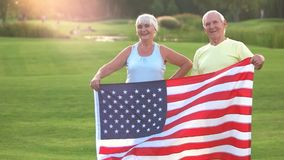 Senior couple holding US flag. Smiling man and woman outdoor. Patriots of strong country. Former olympic champions stock video footage