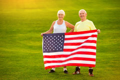 Senior couple holding US flag. Royalty Free Stock Photography