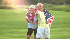 Senior couple holding USA flag. Elderly people show thumb up. Healthy citizens of strong country. Proud to be American stock video