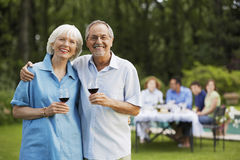Senior Couple Holding Wine Glasses In Backyard Stock Images